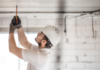 electrician-installer-with-tool-his-hands-working-with-cable-construction-site@2x
